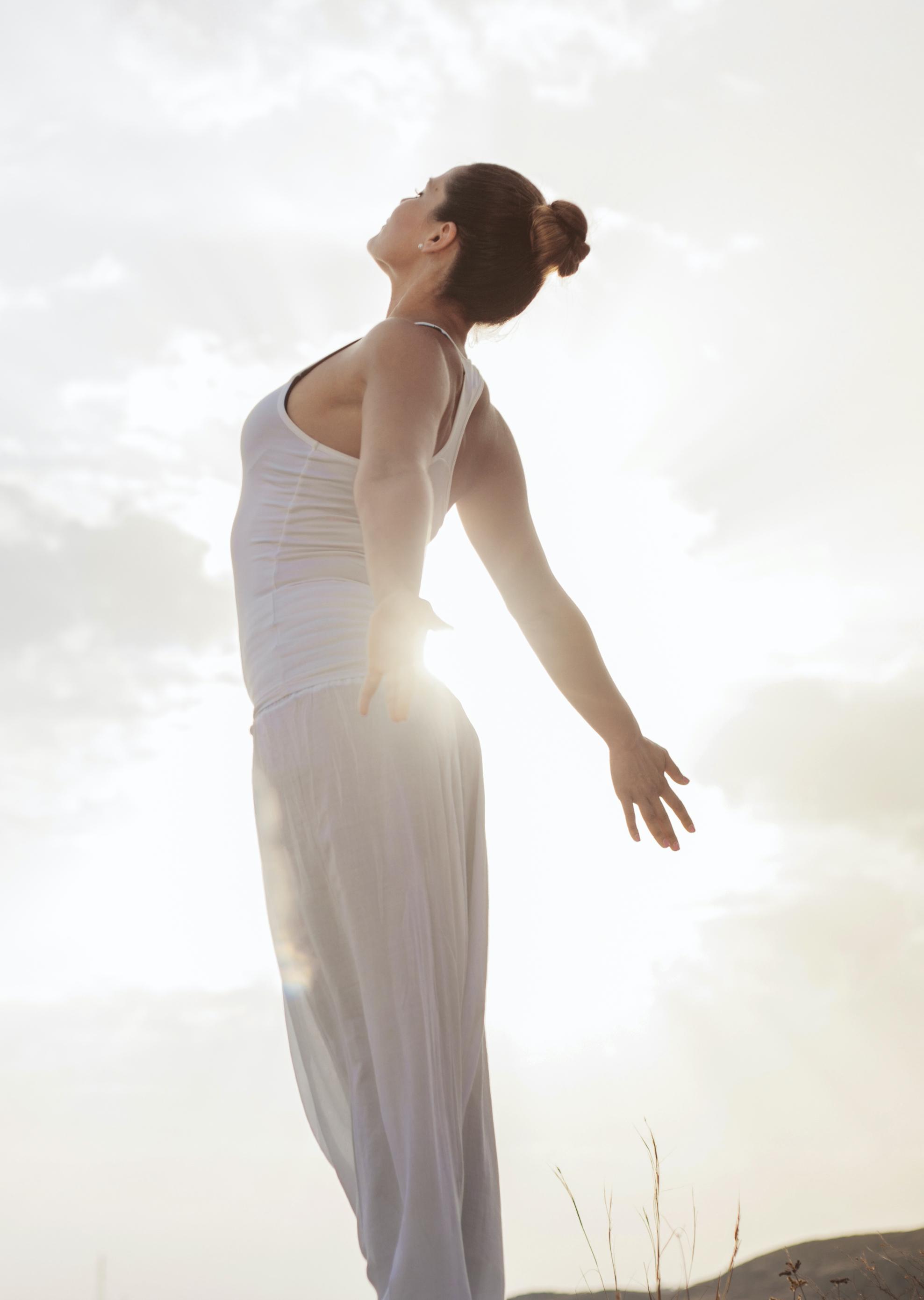femme qui s'étire debout en regardant le ciel