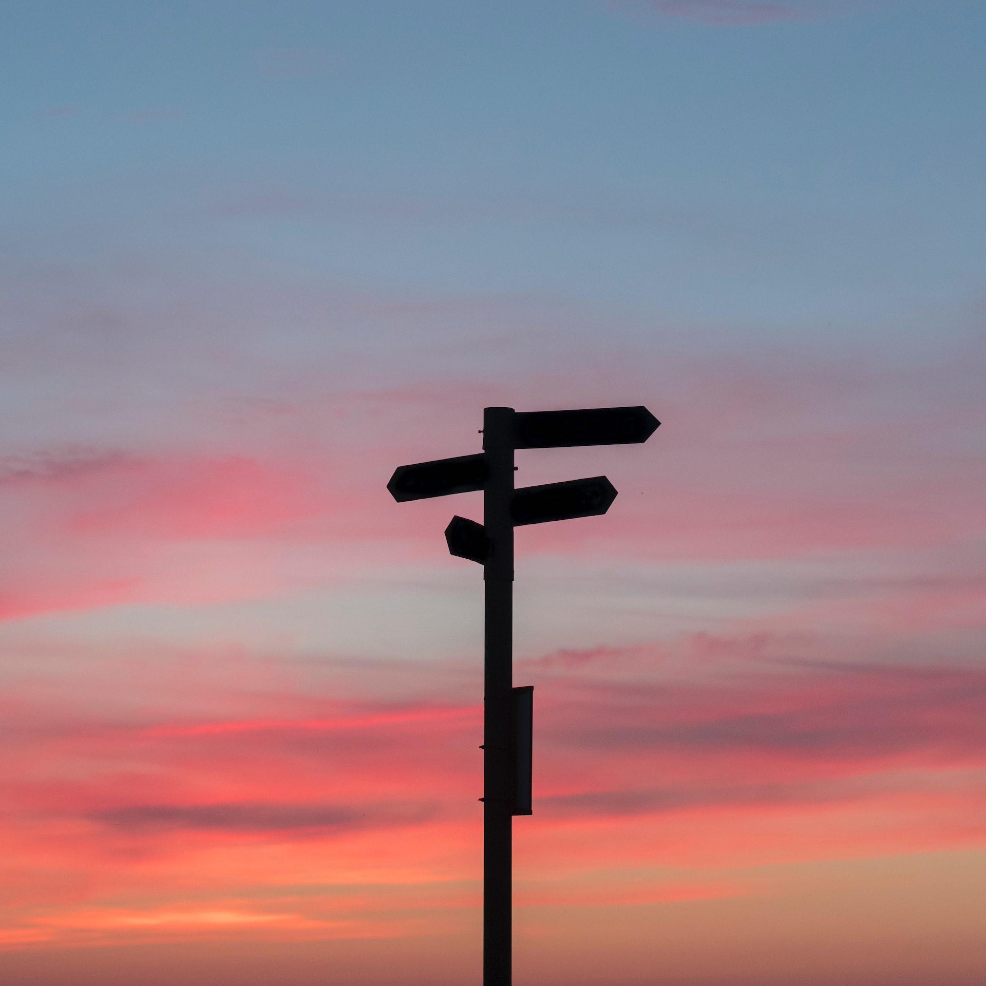 2 panneaux de direction avec soleil couchant